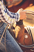 Hand of a cowboy holding his rope and the saddle horn while riding at a summer rodeo.