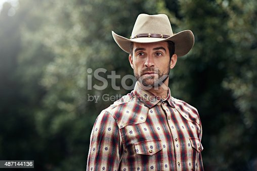 Shot of a handsome cowboy wearing a check shirt and stetsonhttp://195.154.178.81/DATA/i_collage/pi/shoots/784125.jpg