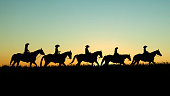 Line of horseback riders in a pasture at sunset.