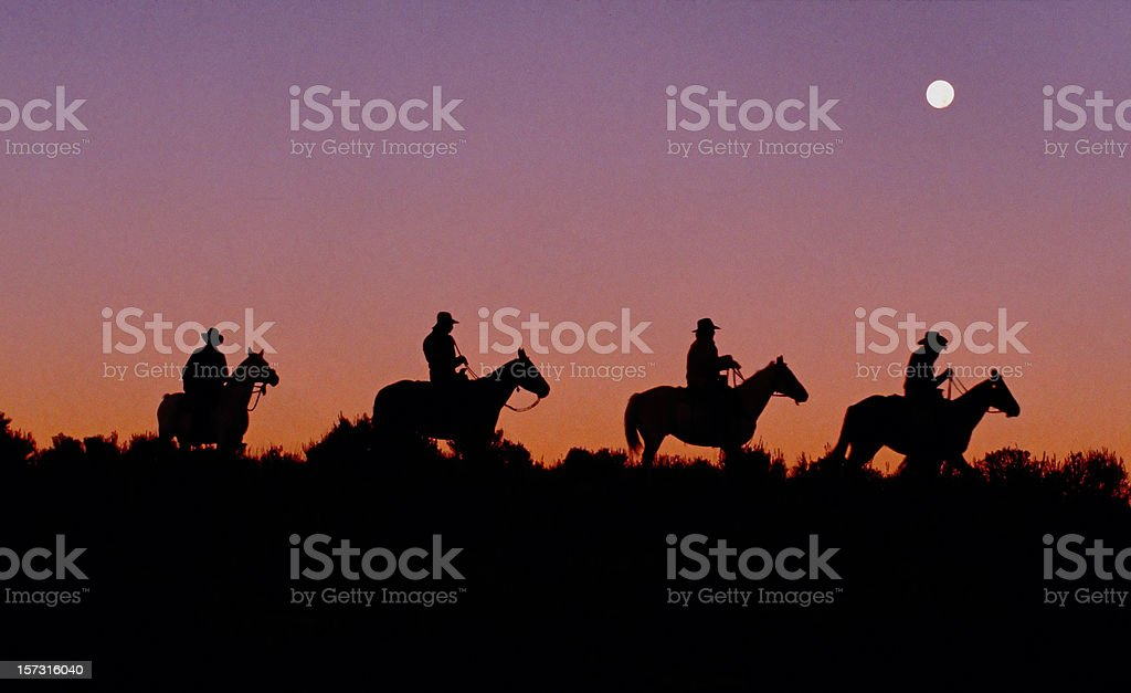 Cowboys on Horseback Ride Ridge, Dawn, Silhouette, Americana, Sunrise royalty-free stock photo
