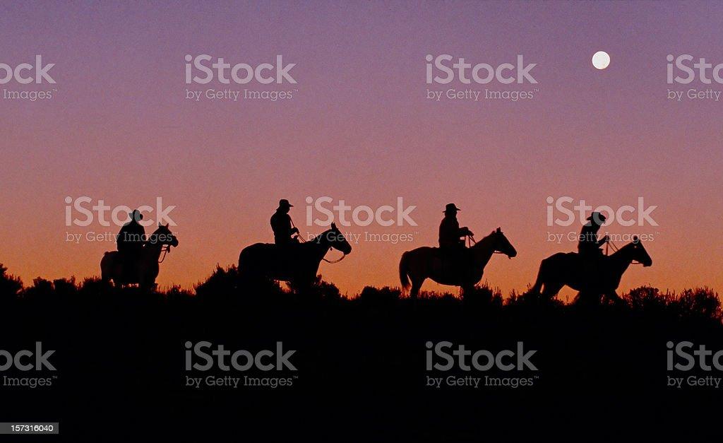 Cowboys on Horseback Ride Ridge, Dawn, Silhouette, Americana, Sunrise stock photo