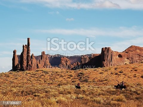 13 october 2018 - Monument Valley, USA: 3 cowboys riding a horse in Monument Valley