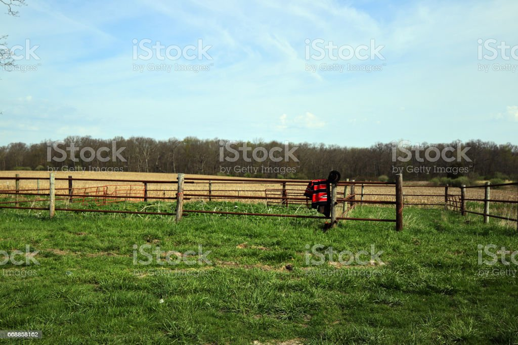 A cowboys saddle blanket, boots, hat and duster hang on the corral fence. stock photo