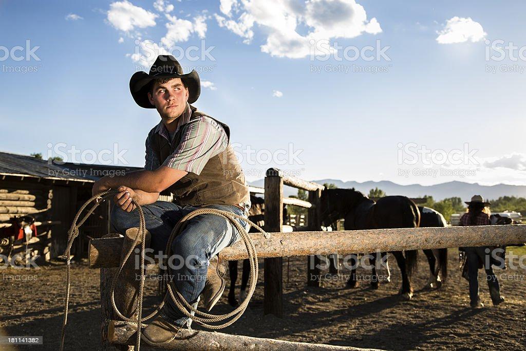 Cowboys: Wrangler on fence at corral.  Cowgirl saddling horse background. royalty-free stock photo