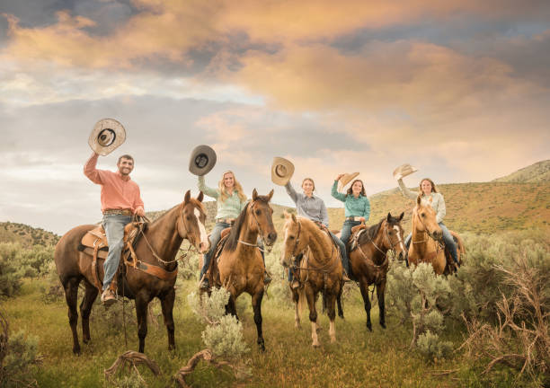 Cowfamily, father, daughters on horses, fields and Utah mountains - foto stock