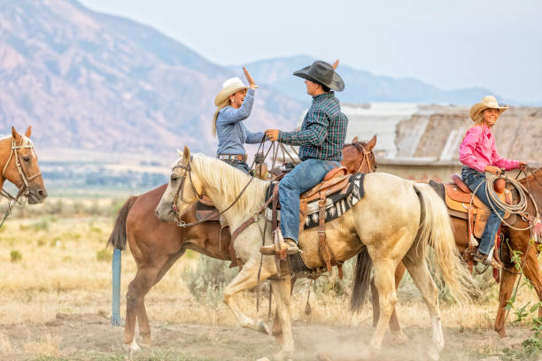 Cowgirl and cowboy congratulate each other while on horseback stock photo