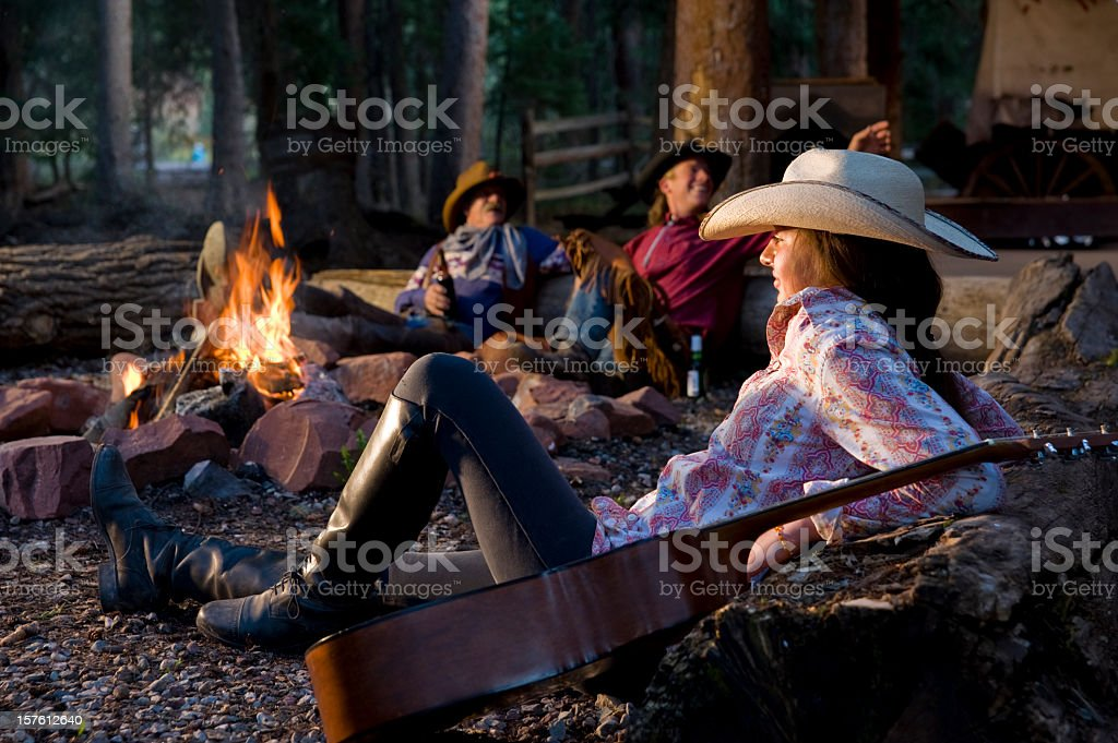 Cowgirl and Cowboys sit around fire with guitar royalty-free stock photo