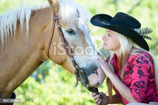 Cowgirl patting her horse on the nose close up.