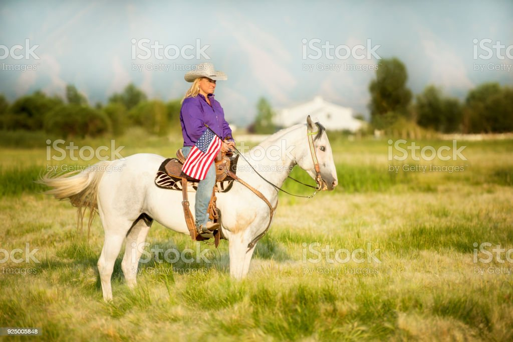 Cowgirl Astride Her Horse In A Lush Green Valley Nestled At The Base of The Rocky Mountains.  She is sitting quietly holding an American Flag. Late Afternoon. stock photo