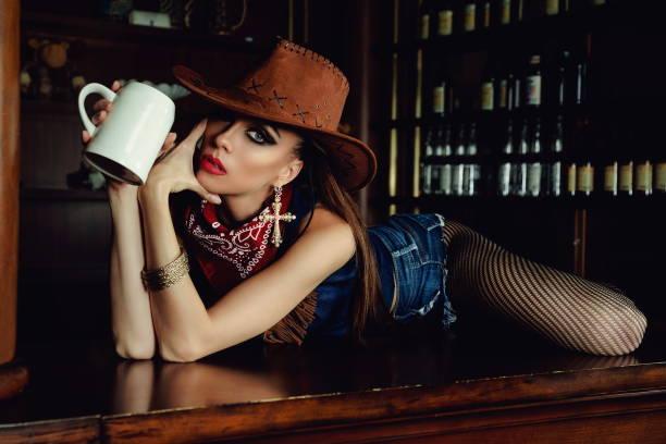 ein cowgirl an der bar. - bier kostüm stock-fotos und bilder