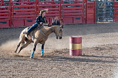 Cowgirl barrel racing at rodeo