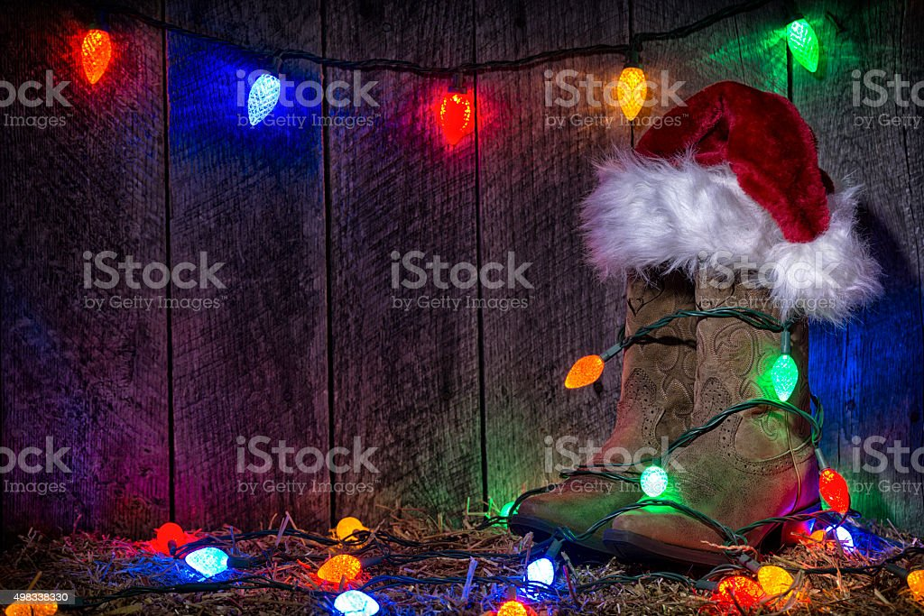 Cowgirl Boots at Christmas time with lights and Santa Hat stock photo