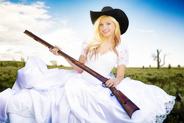 cowgirl braut halten schrotflinte in montana gestrüppland - shotgun wedding stock-fotos und bilder