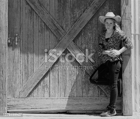Cowgirl leaning on rustic barn door, copy space, black & white. Horizontal.