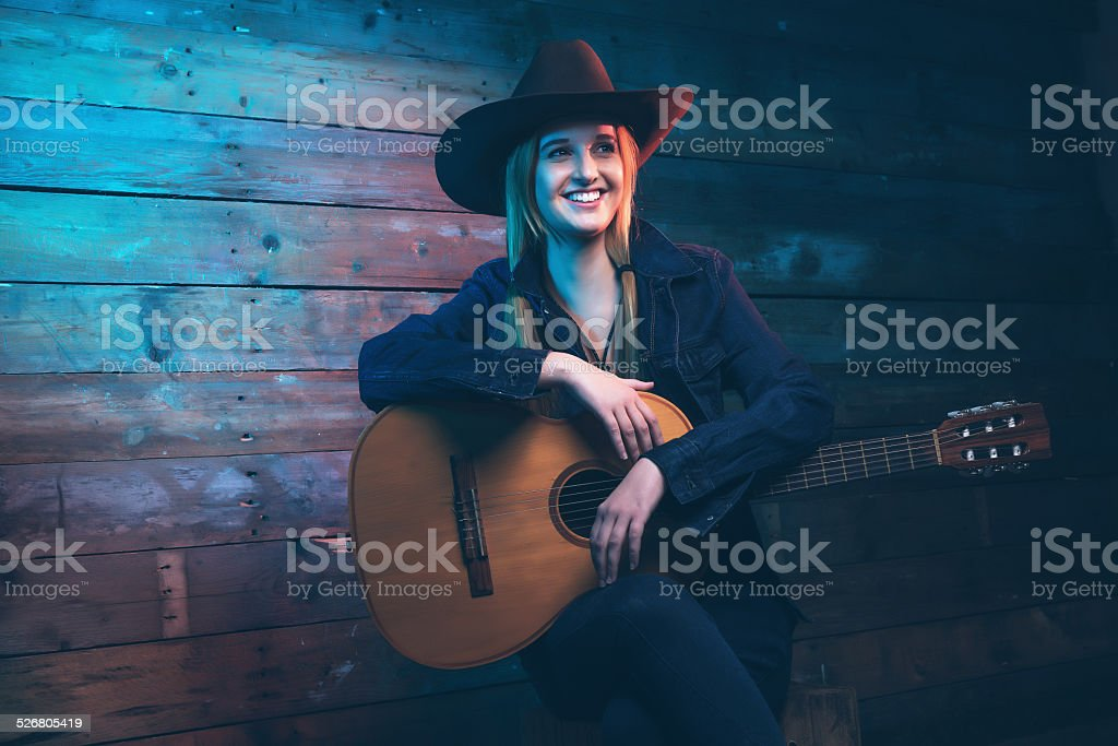 Cowgirl country singer with acoustic guitar. Wearing blue jeans. stock photo