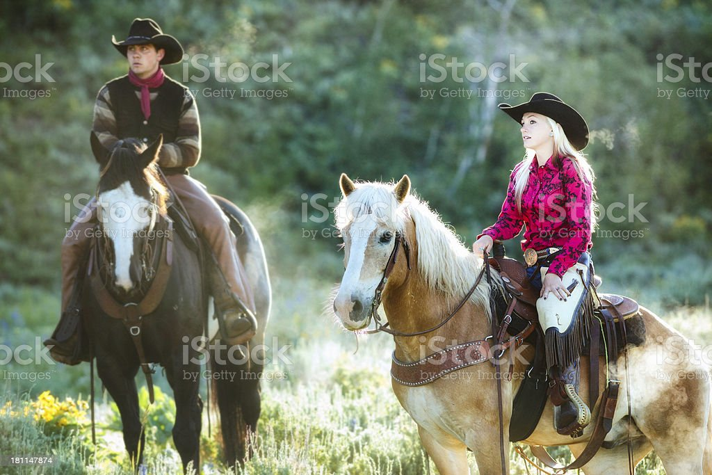 Cowgirl discusses approach for herding with cowboy royalty-free stock photo