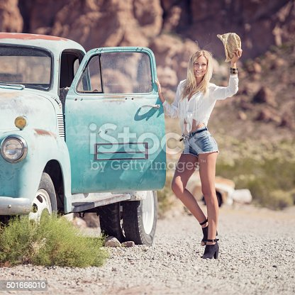 Beautiful model posing beside an Oldtimer in the middle of the desert.