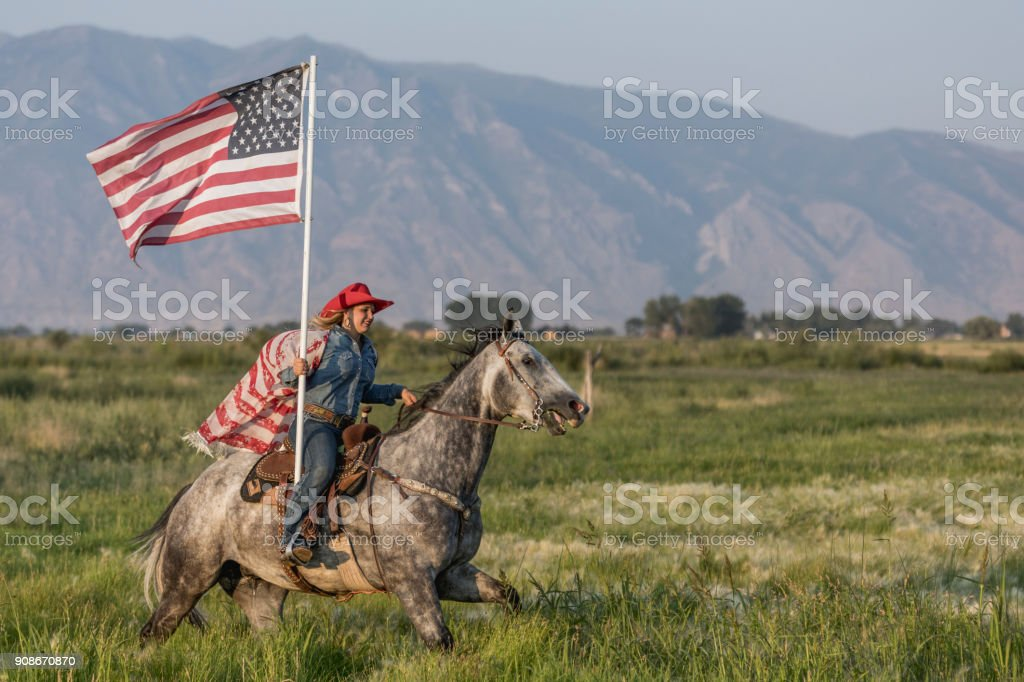 Cowgirl horseback riding while proudly holding the American flag. stock photo