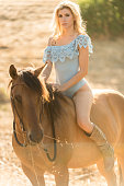 istock Cowgirl In A Sexy Outfit Riding Her Horse 819438372