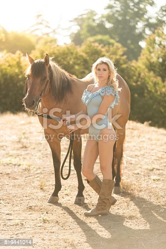 Cowgirl In A Sexy Outfit Riding Her Horse with cowboy boots on.