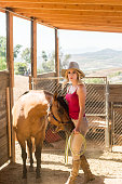 istock Cowgirl In The Stables With Her Horse 819438110