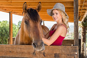 istock Cowgirl In The Stables With Her Horse 819438338