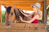 istock Cowgirl In The Stables With Her Horse 819438494