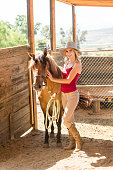 istock Cowgirl In The Stables With Her Horse 819438556