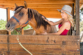 istock Cowgirl In The Stables With Her Horse 819440720