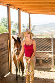 istock Cowgirl In The Stables With Her Horse 819441182