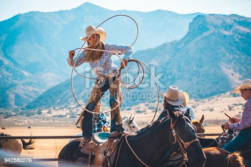 Cowgirl is riding a horse in rodeo arena in Utah, USA.