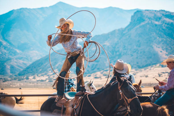 Cowgirl lassoing in rodeo arena stock photo