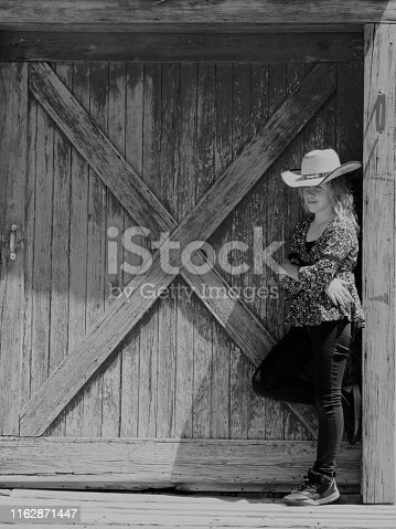 Cowgirl leaning on rustic barn door, copy space, black & white