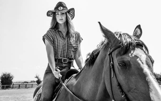 Cowgirl looking at camera while riding horse with western saddle and hat stock photo