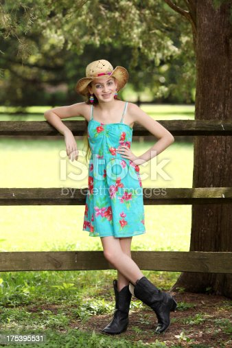 Teenage girl in a sundress cowboy had and cowboy boots.