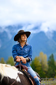 Portrait of a modern cowgirl. Female rancher riding a horse. Women working in agriculture.