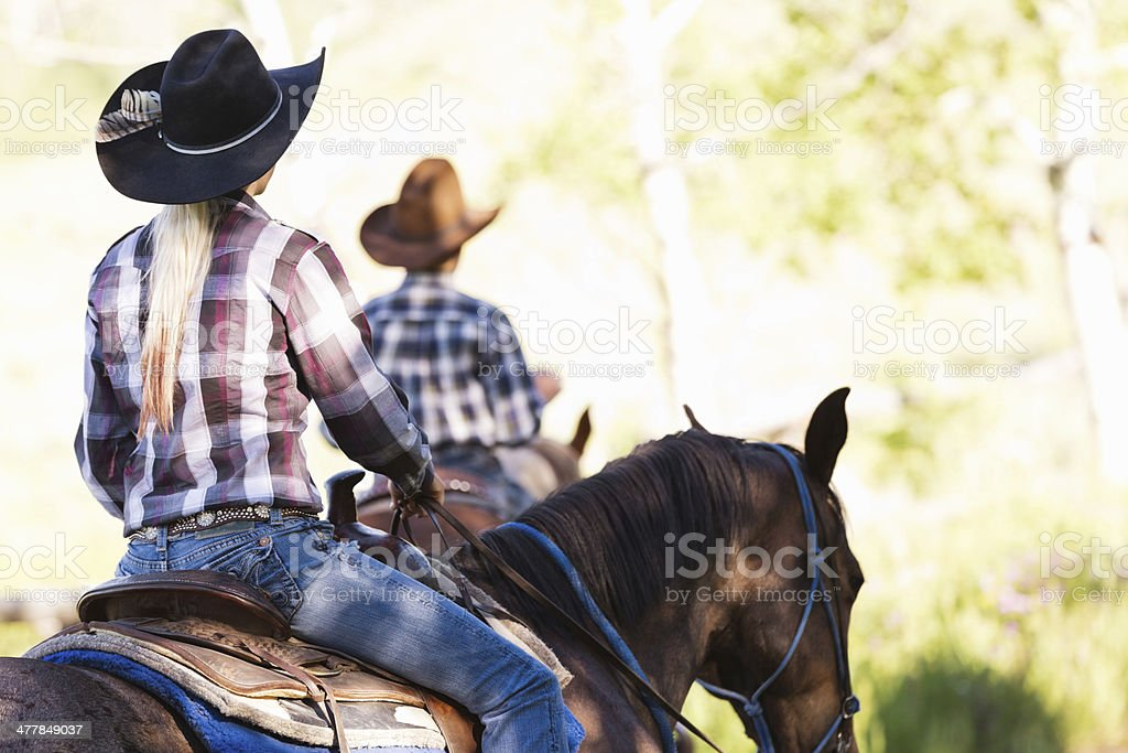 Cowgirl riding horse during ranch trail ride stock photo