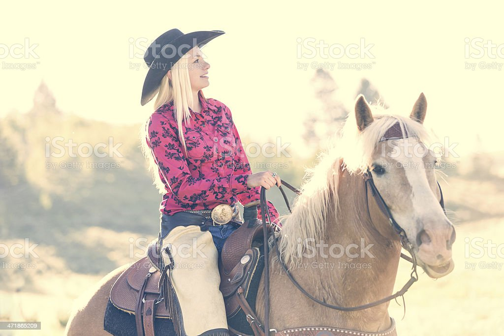 Cowgirl riding horse on ranch at sunset royalty-free stock photo