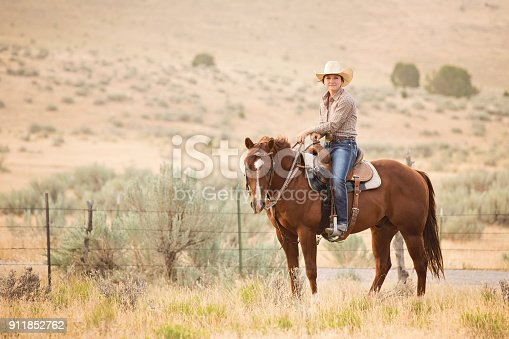 Cowgirl sitting on her quarter horse and posing for the camera. Real people.