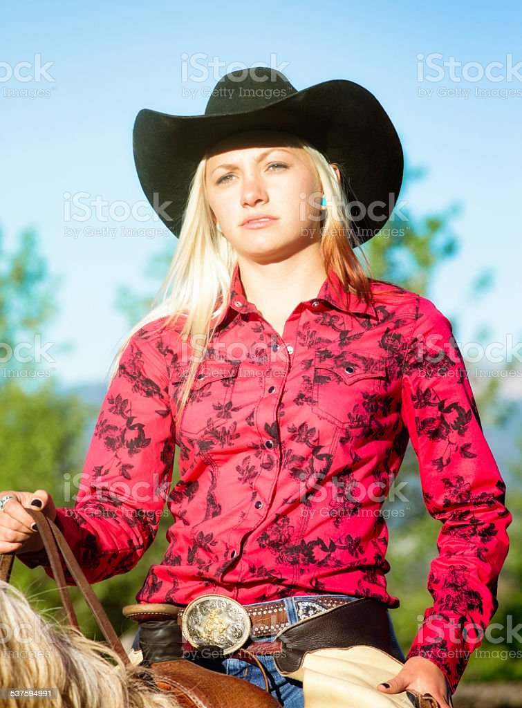 Cowgirl riding with a sad expression stock photo