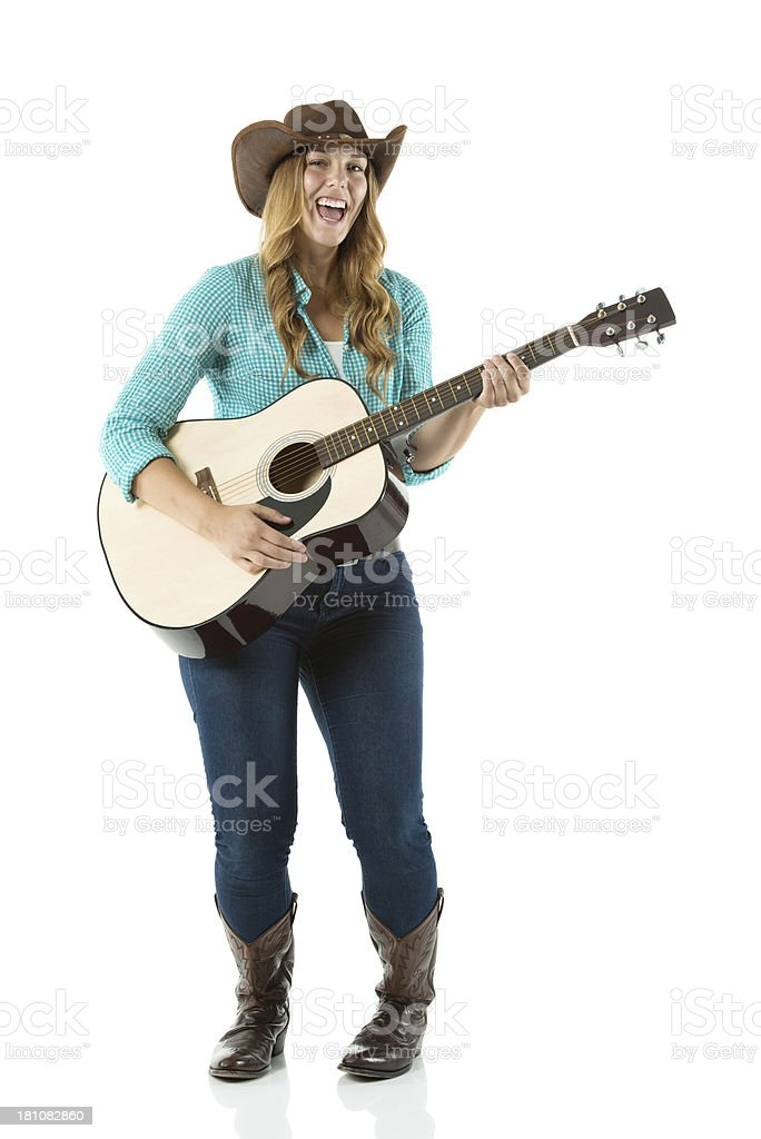 Cowgirl singing while playing a guitar royalty-free stock photo