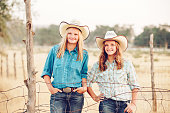 Cowgirl Sisters Smiling By A Wire Pasture Fence