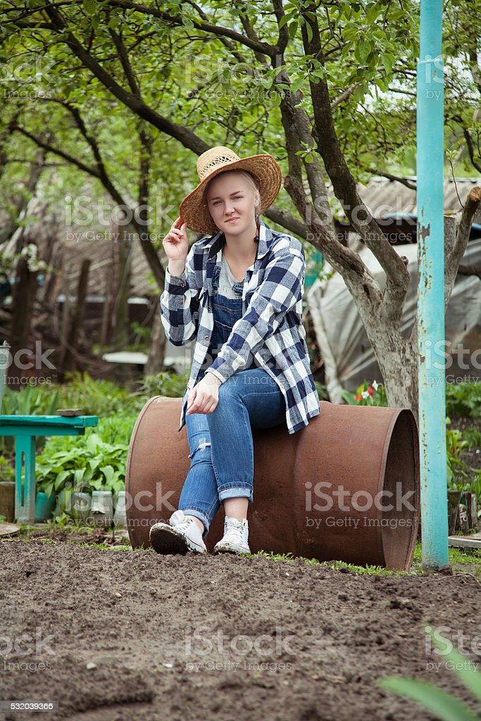 cowgirl sitting on a rustic iron barrel in the garden stock photo