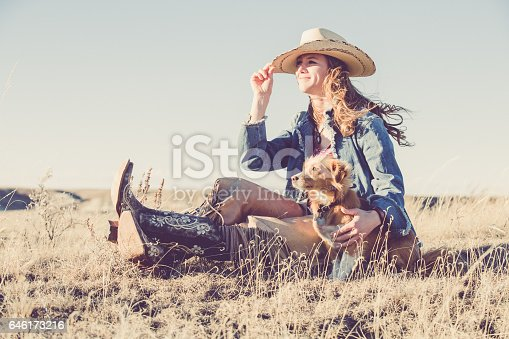 A pretty cowgirl sitting on a grassy prairie, holding her hat with one hand and her little pet dog with the other while looking off into the distance. She is wearing black cowgirl boots, leather chaps, denim jacket and a white cowgirl hat.
