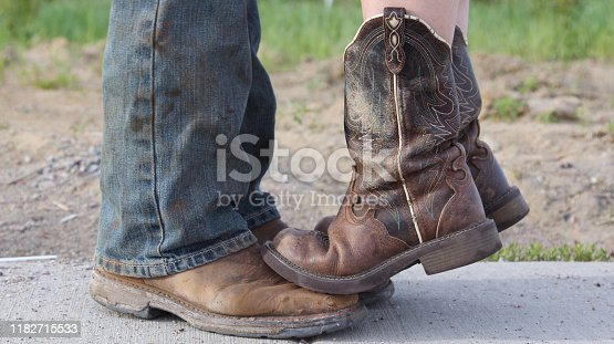 Couple standing together.  Country girl standing on tiptoes on her man's boots.