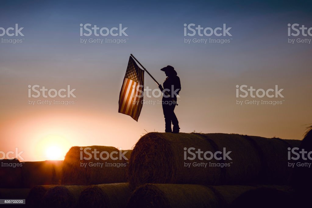 Cowgirl Standing On Top  Bales Of Hay Holding An American Flag stock photo