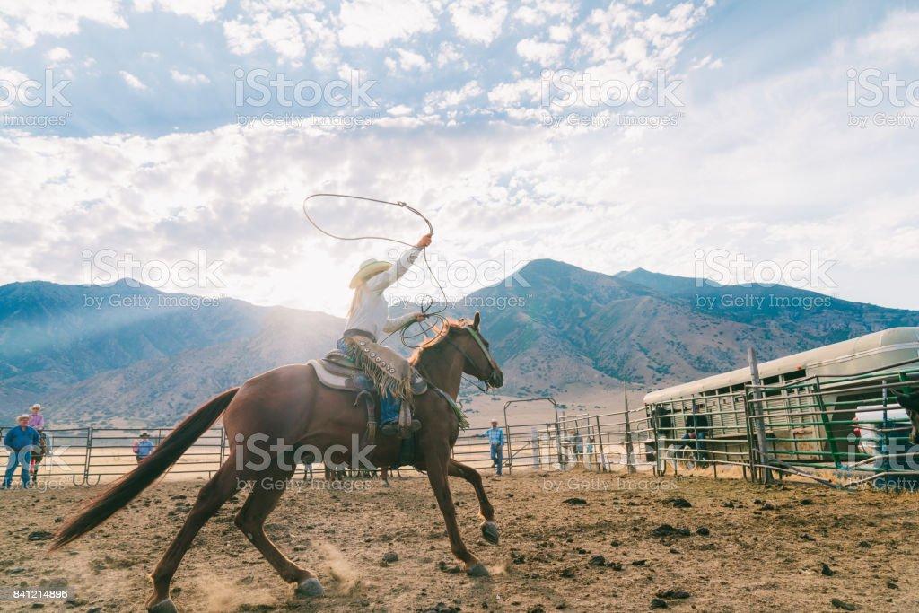 Cow-girl se balançant son lasso prêt à attraper un veau pour marquage à chaud - Photo