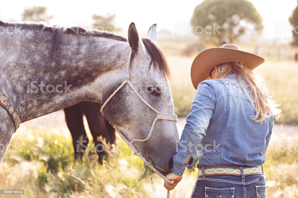 Cowgirl Talking To Her Horse stock photo
