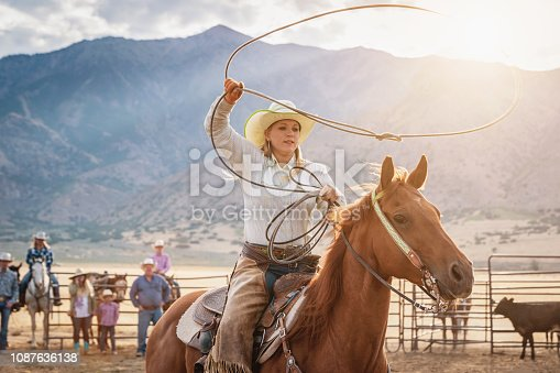 Cowgirl chasing bull riding on her horse, swinging and throwing lasso. Trying to catch the bull in rodeo training. Lassoing training at rural Rodeo Arena. Real People Portrait. Utah, USA.