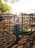 Cowgirl using her phone at a ranch